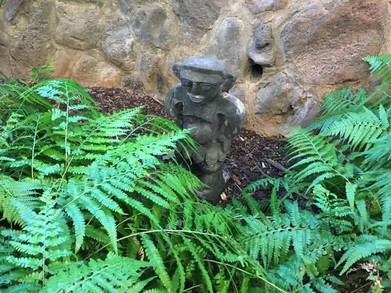 This Menehune is found near a wall along a garden path at the Aulani