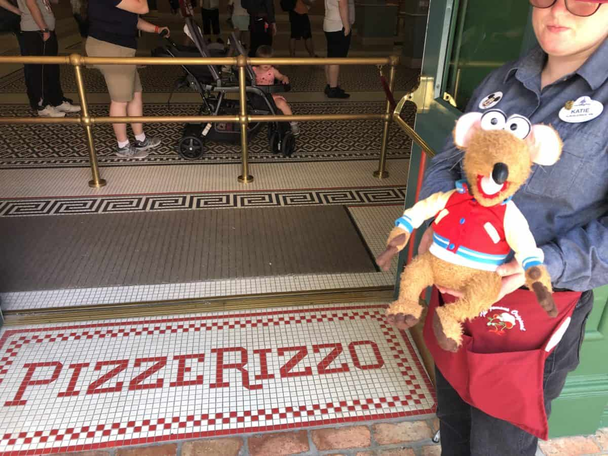 A Cast Member is greeting guests of PizzeRizzo with a stuffed Rizzo plush
